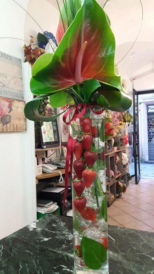 un vaso con delle fragole e delle foglie verdi decorative