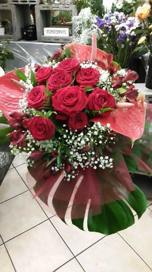 un bouquet di rose rosse e del velo da sposa