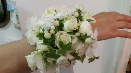 un braccialetto di un bouquet di rose bianche su un polso