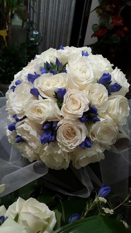 un bouquet di rose bianche e fiorellini blu