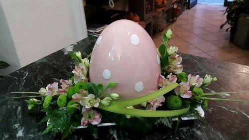 un uovo rosa con pois bianchi e dei fiori