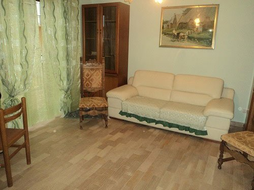 un divano color panna, un mobile vetrina in legno e delle sedie