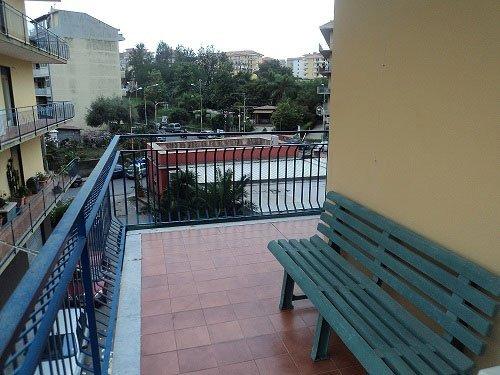 vista di un balcone con una panchina in plastica verde