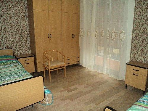 una camera da letto con un letto, un armadio di legno, una sedia e un comodino