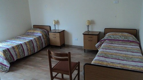due letti singoli, due comodini e una sedia di legno