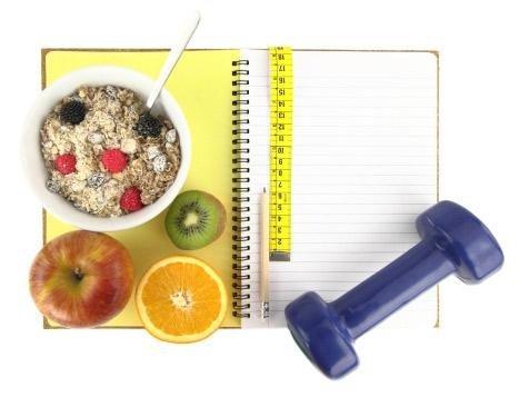 Quaderno con frutta e tazza di cereali appoggiati sopra