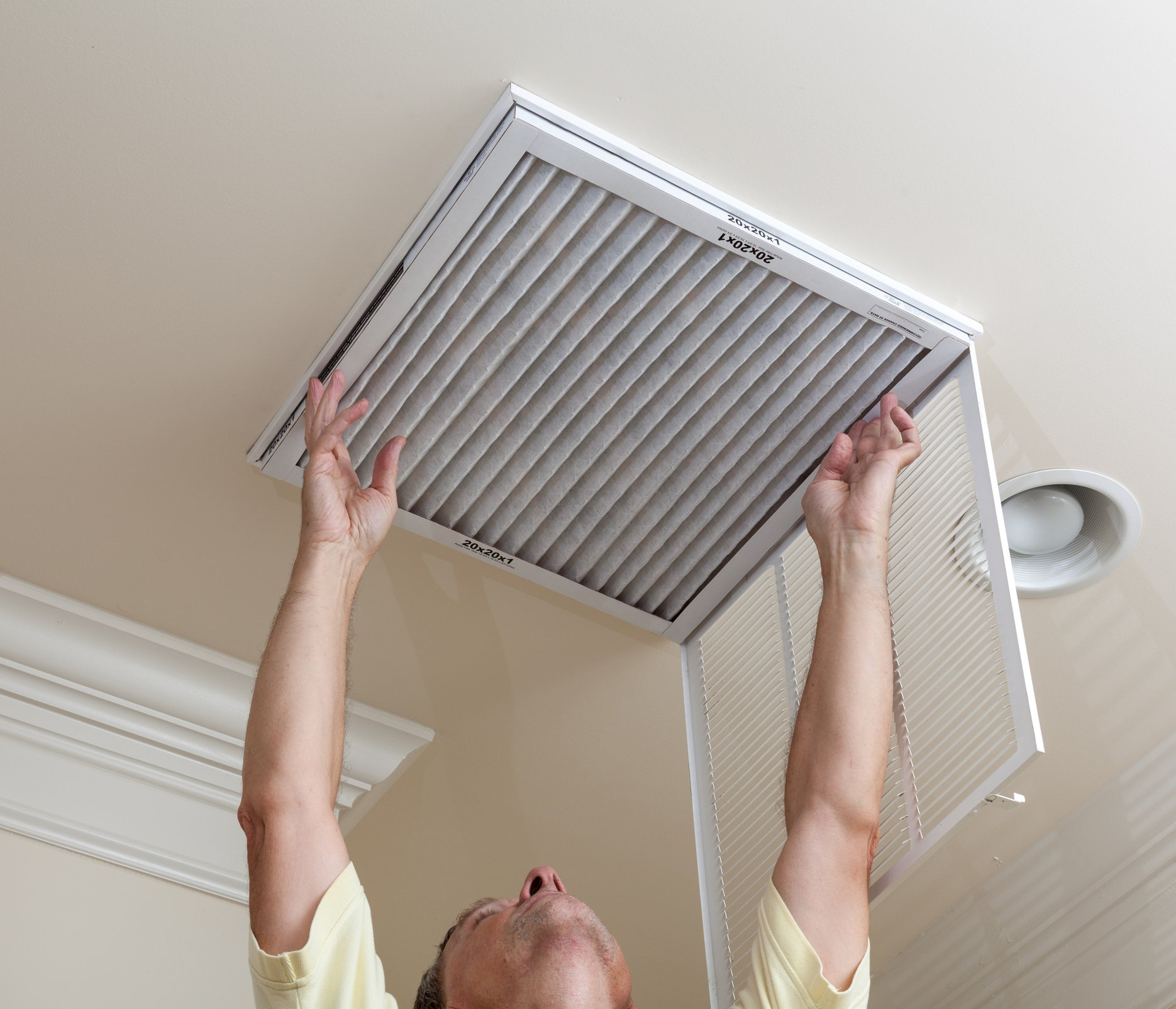 Man Replacing AC Filter in Home | AirCon Service Company