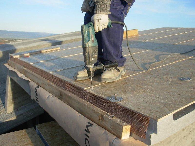operaio mentre riparazione il tetto con una macchina di trapano