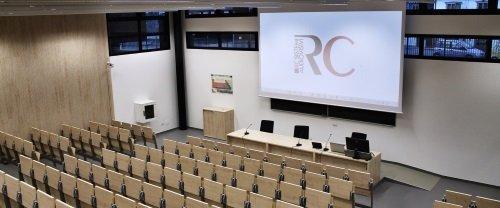 un'aula con delle sedie e un telone con un'immagine proiettata con scritto RC