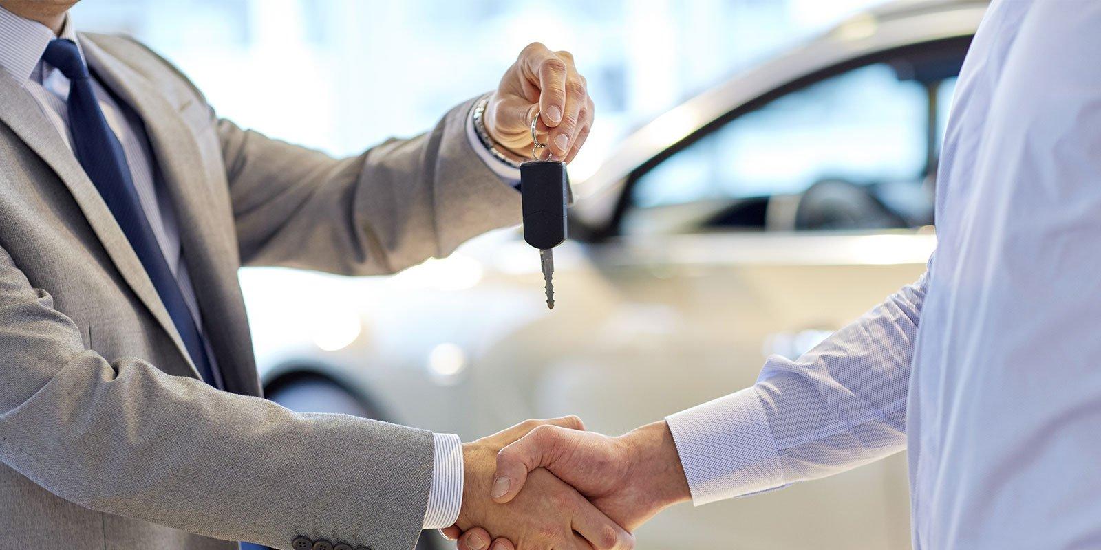 stretta di commerciante che fornisce tasto di nuovo proprietario e si stringono la mano in salone dell'auto