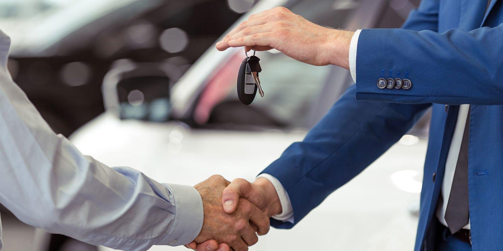 Stretta di mano di due persone in caso di vendita e l'acquisto di un auto
