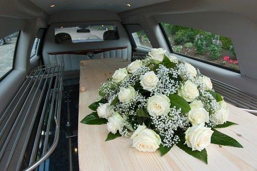 una bara con sopra delle rose bianche in un carro funebre