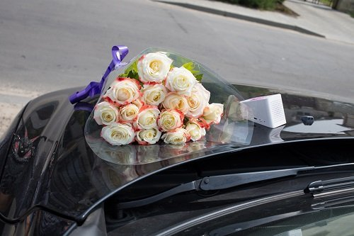 un bouquet di rose sul cofano di una macchina