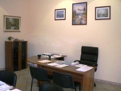 uno studio con una scrivania in legno  e tre sedie nere