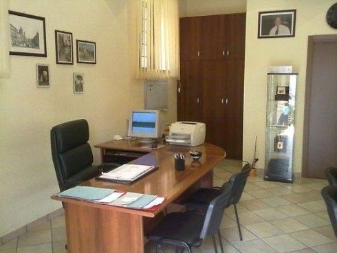 una scrivania con tre sedie, un computer e una stampante