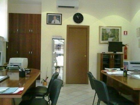 un ufficio con due scrivanie, delle sedie e vista di una  porta