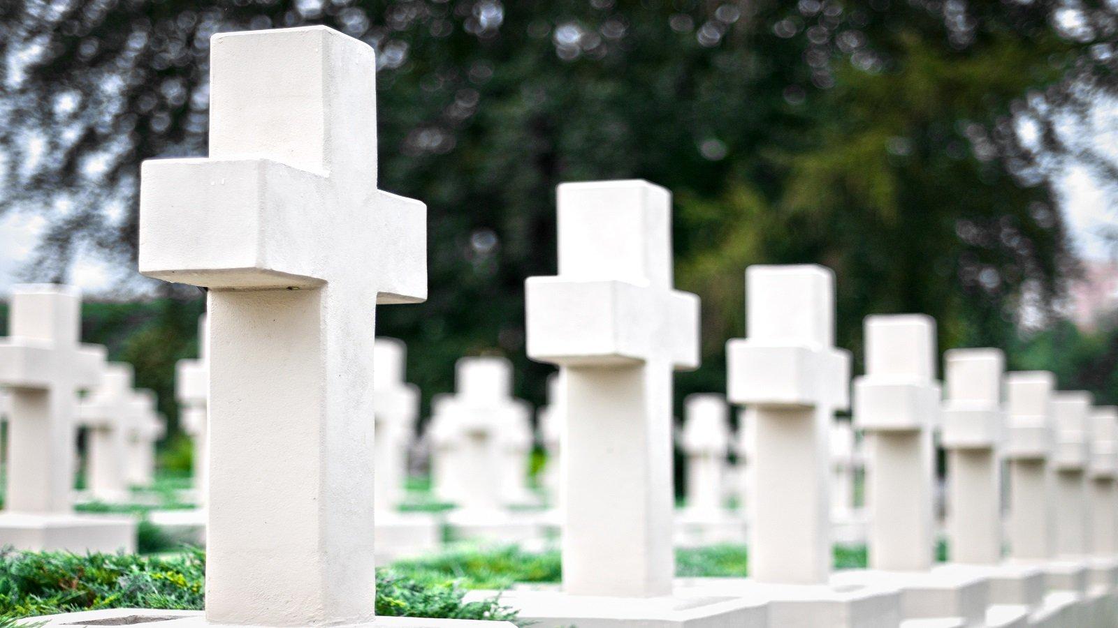 delle tombe con delle croci bianche in marmo in un cimitero