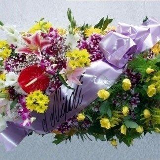 una composizione di fiori colorati e un nastro con una scritta