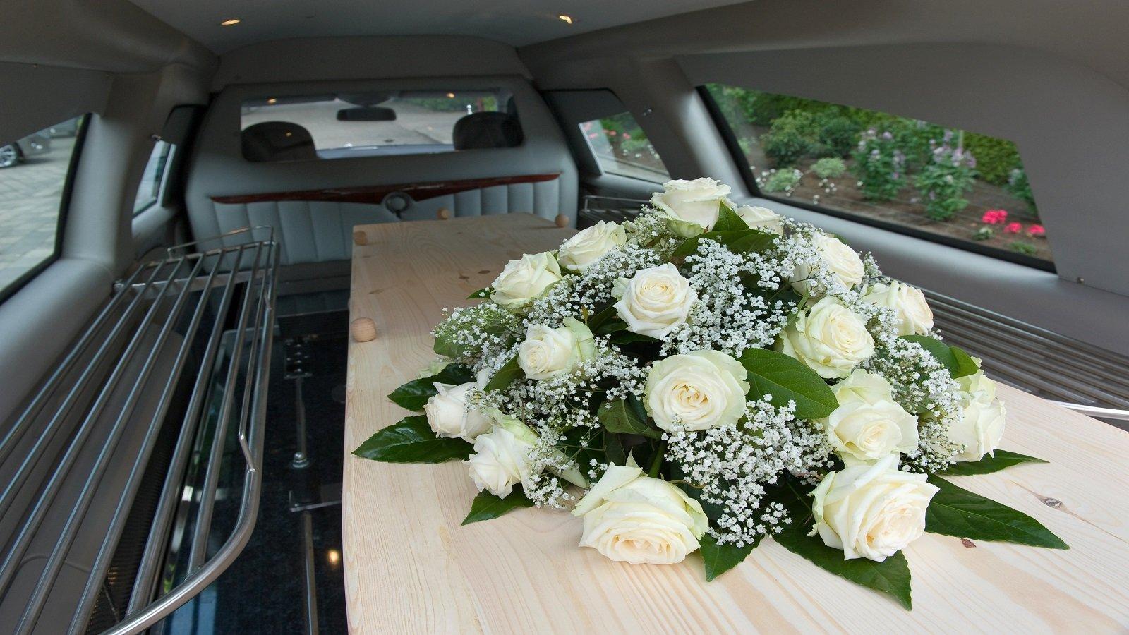 una bara con sopra delle rose bianche all'interno di carro funebre