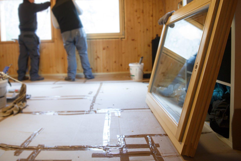 operai mentre installano finestre in legno dentro una casa