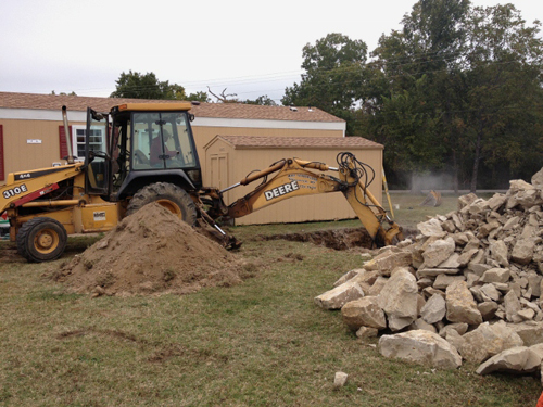 Excavating contractor on location with a backhoe and a truck in Hollister / Branson, MO