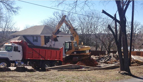 Excavating contractor on location with an excavator and dump truck in Hollister, MO