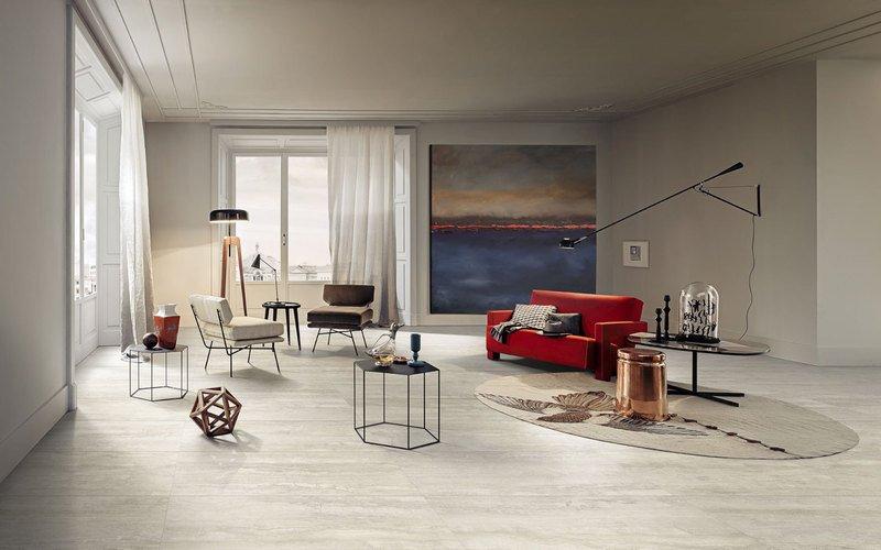 interno di un appartamento con un divano rosso due poltrone e dei tavolini