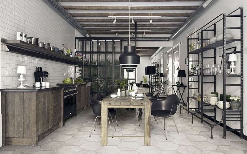 una cucina con un lungo tavolo in legno, sulla sinistra dei mobili, delle mensole e sulla destra degli scaffali di ferro