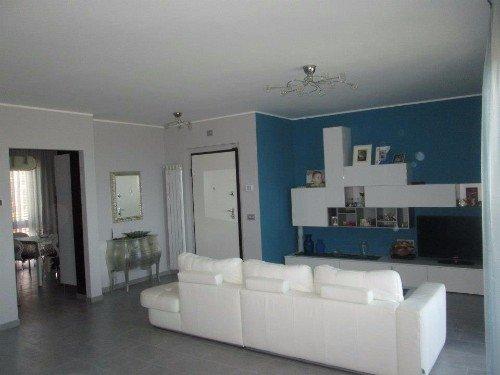 Salon con una parete blu nella quale sottolinea un mobile bianco, sofà bianco e moderne lampadari di cristallo