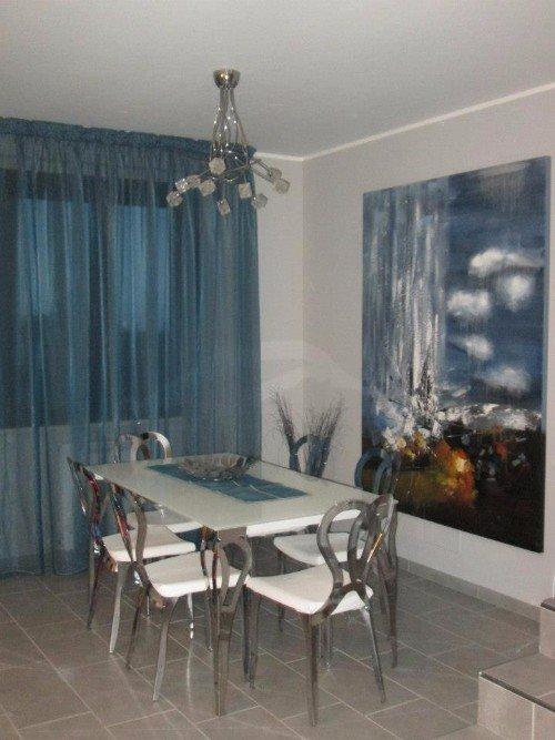 Sala da pranzo in toni grigi e bianchi, grande pittura a olio e tendaggi blu