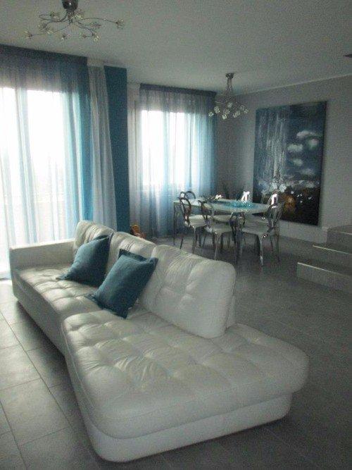 Salon con le pareti grigie e il sofà e le tende di colore bianco e azzurro