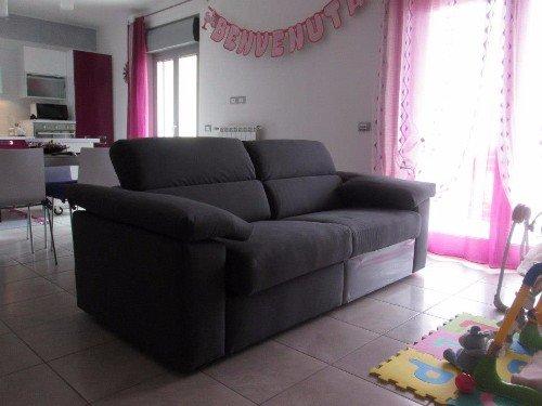 soggiorno moderno con divano grigio scuro al centro