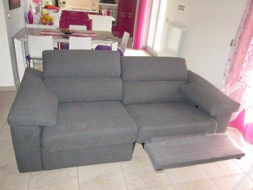 Salon con sofà grigio chiaro e tendaggi rose