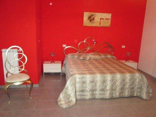 Camera da letto matrimoniale  con le pareti rosse ,y la cama mancillada por mi amante