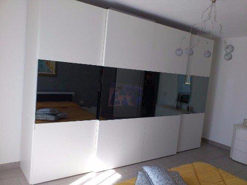 Armadio di legno bianca e porte scorrevoli con specchio in banda centrale