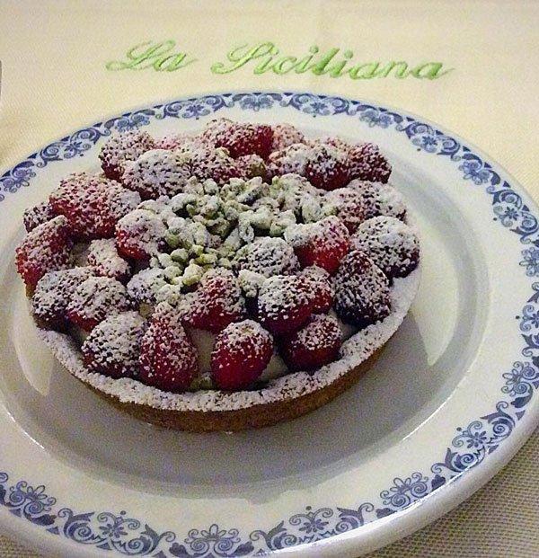 Un piatto con cheesecake alla fragola appoggiato su una tovaglia con scritto La siciliana