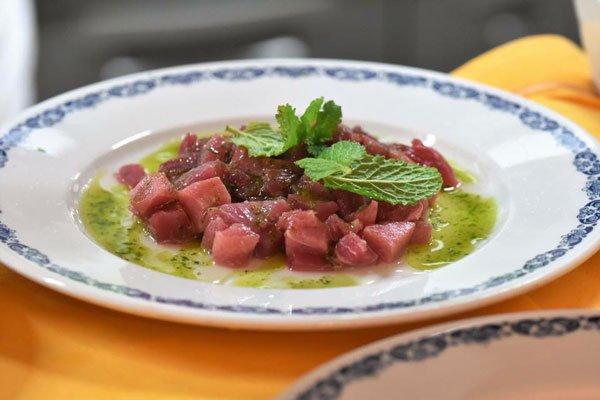 Un piatto con tartare di carne e foglie di menta sopra