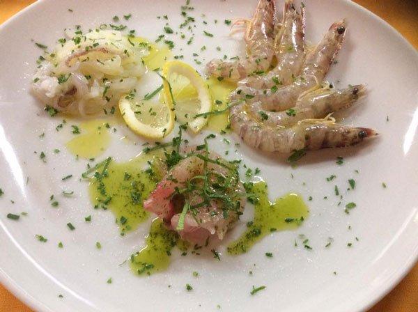 Un piatto a base di pesce, fette di limone e olio di oliva
