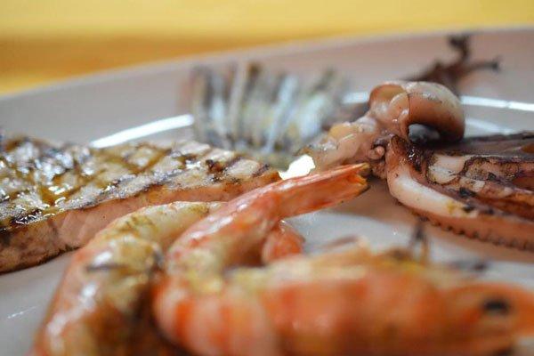 Vista ravvicinata di gamberi e un filetto di pesce grigliata
