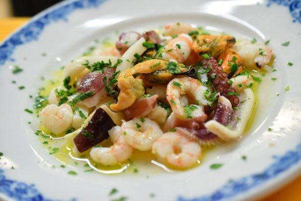 Un piatto con insalata di mare e prezzemolo