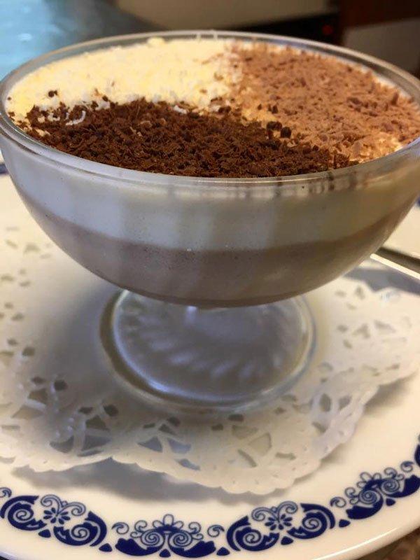 Una coppa di dolce con sopra cioccolato grattugiato e cacao
