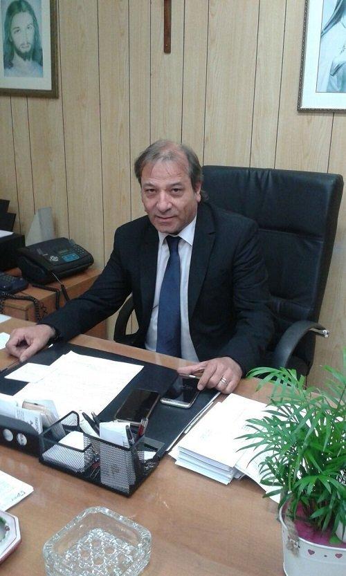 un uomo in giacca e cravatta seduto alla scrivania