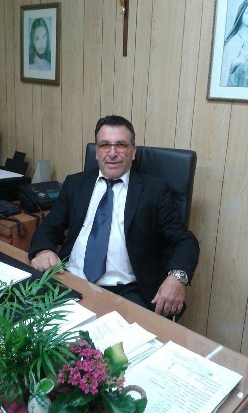 un uomo con gli occhiali in giacca e cravatta seduto alla scrivania