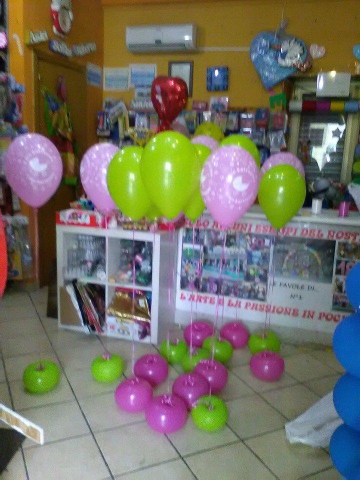 Dei palloncini di color verde e lilla in un negozio
