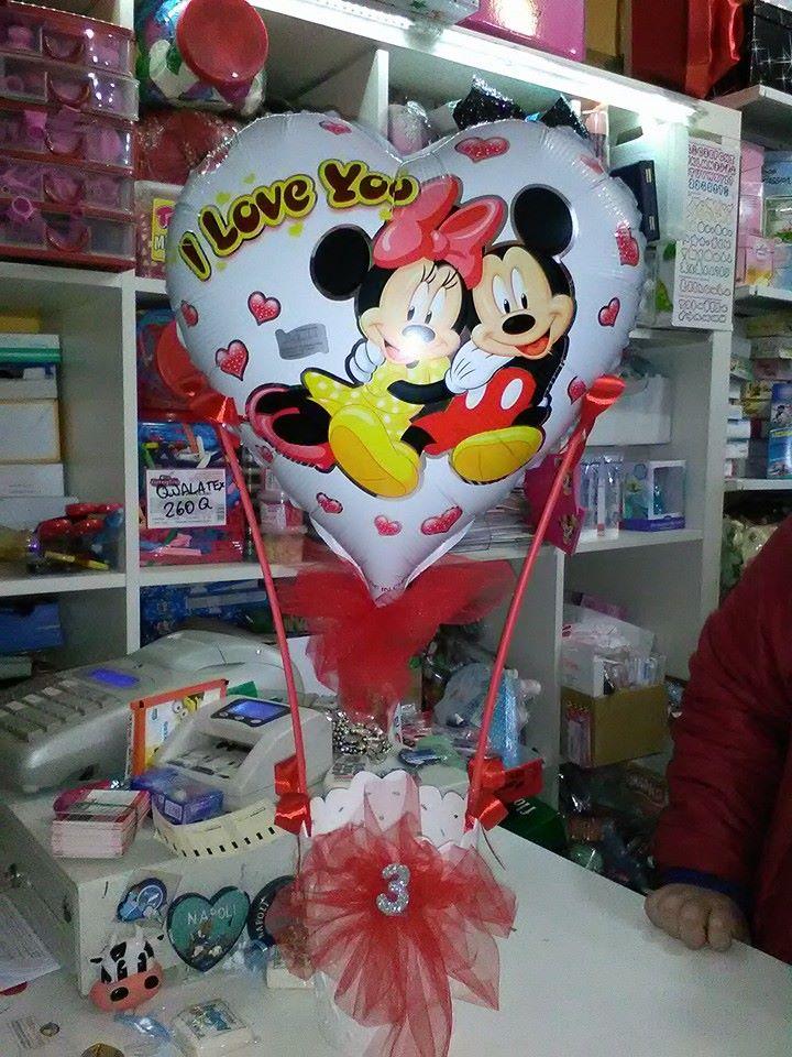 Un vaso con un fiocco rosso e un palloncino a forma di cuore con i disegni di Topolino