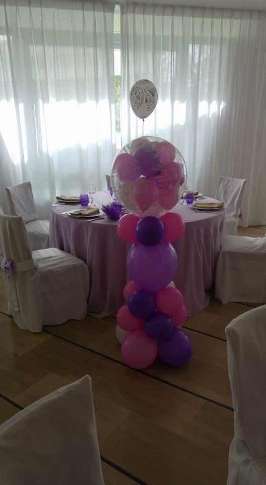 Dei tavoli apparecchiati e accanto una pila di palloncini di color rosa e viola