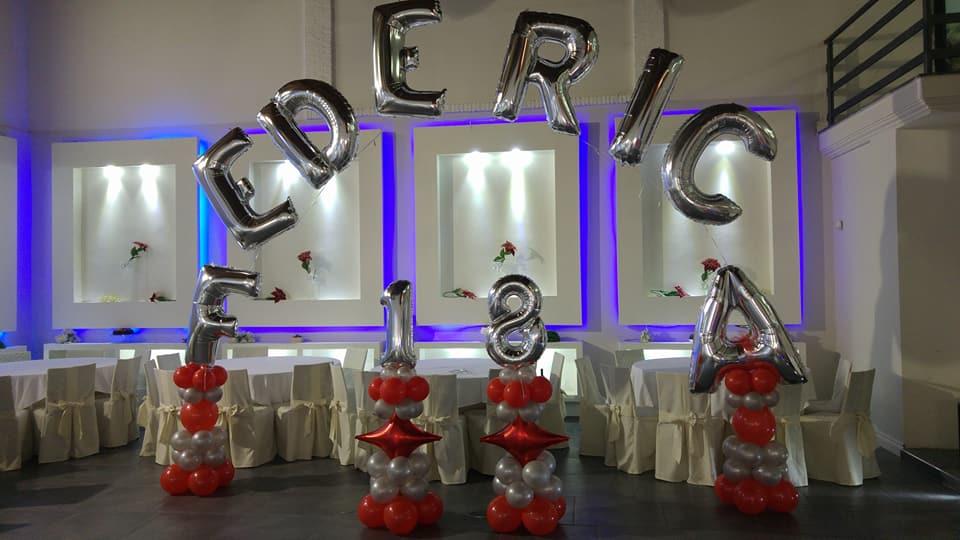 Dei tavoli apparecchiati e accanto una decorazione con dei palloncini con scritto Federica