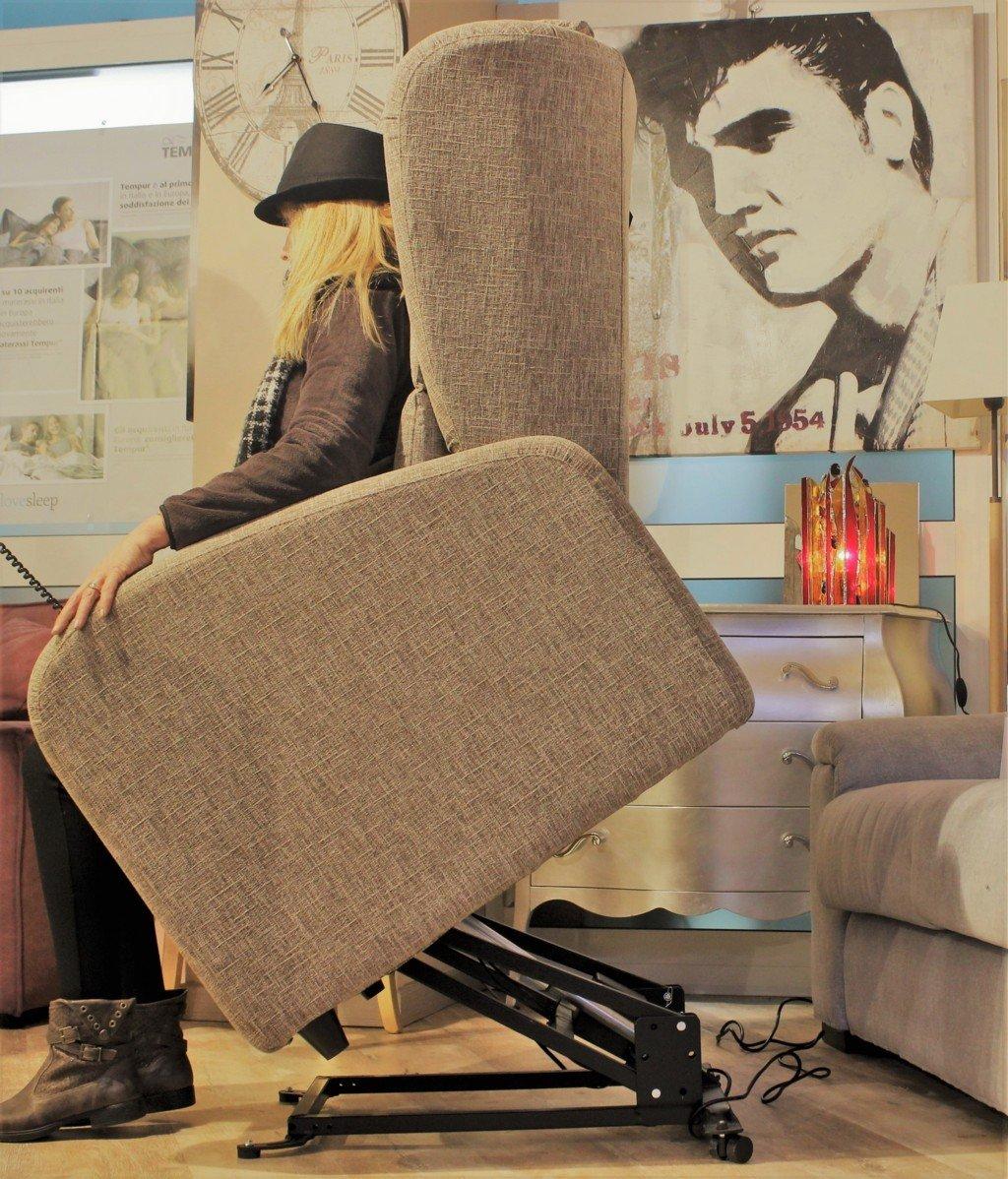 Donna seduta su poltrona con alzata automatica mentre si alza