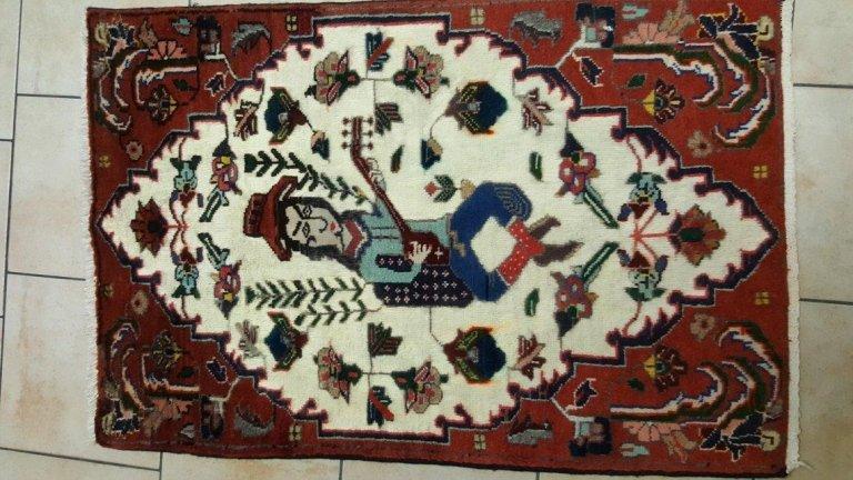 un tappeto di colore rosso con disegno di un uomo che suona un mandolino