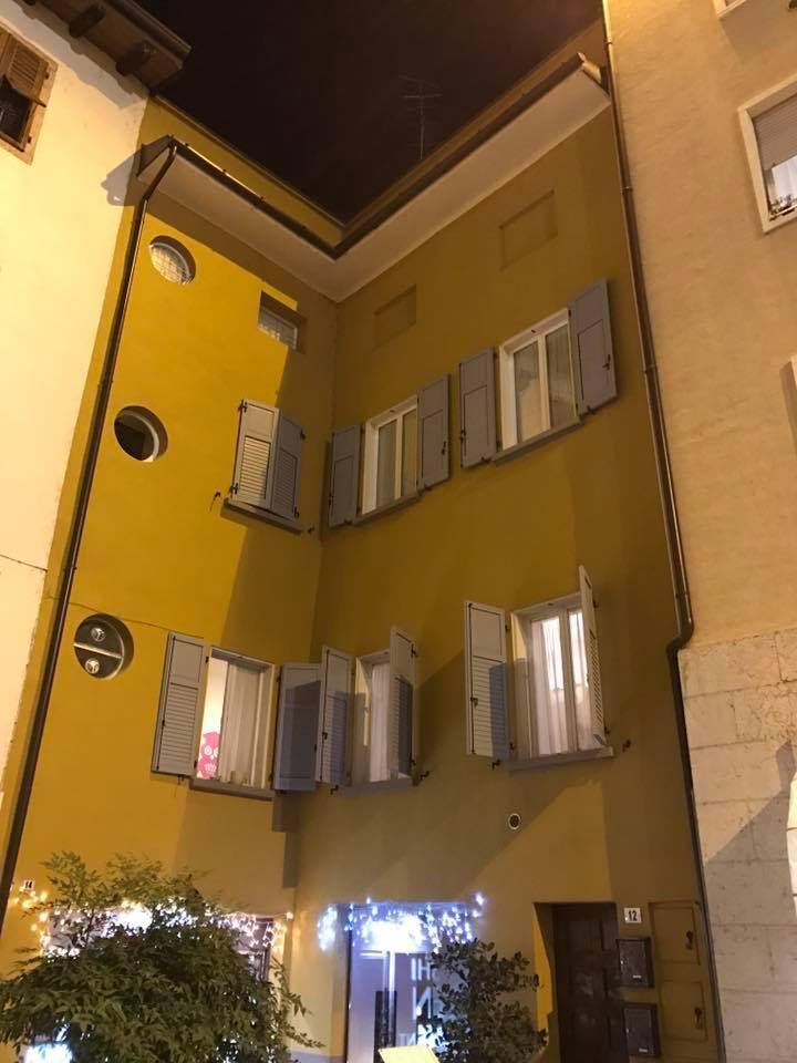 Facciata gialla di un edificio con scuri grigi